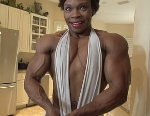 Female bodybuilder Nadia poses for you so you can get a good look at her ripped ebony abs, vascular biceps, and muscular pecs, legs, glutes and at her calves in clear high heels. I'm getting so turned on, she moans, as she masturbates her big clit with a toy. Aren't you?