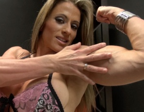 Female bodybuilder Maria G is posing for you in the bedroom in pink panties and high-heeled shoes, showing you her powerful pecs and the muscles of her vascular biceps and ripped abs.