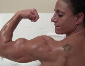 Female bodybuilder Miss Lisa is enjoying her bubble bath after her workout. She's liking the warm water on her big, vascular biceps and tired feet and posing to show you how good the muscles of her ripped abs, legs and glutes look, her tattoos and her muscle control of her pecs. Want to get wet with her?