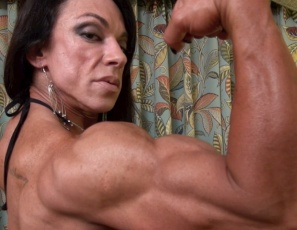 Female bodybuilder Carla poses for you in the bedroom, showing you her powerful pecs, big, vascular biceps and ripped abs, and her muscle control of her tattooed legs and glutes. Could she control you?