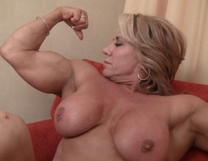 Female bodybuilder Li'l Doll is posing nude and barefoot in panties, showing off the mature muscles of her pecs, legs, glutes and biceps, and using a toy to masturbate her big clit while you watch in close-up.
