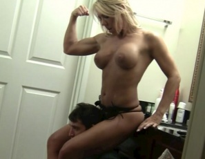 Samantha's using her muscular legs and glutes to scissor and her bare feet to give a foot job while she poses and flexes her pecs and biceps, then makes her servant masturbate with her feet and gives him a bicep job and hand job. Watch the tenderizing CBT and muscle porn in close-up.