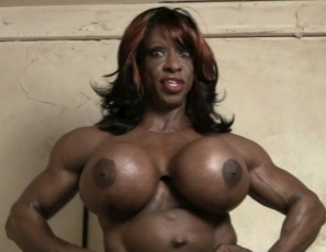 Female bodybuilder Yvette Bova got herself a monster ebony strap-on, and she's posing with it, showing off her vascular, muscular pecs, biceps, abs and legs, and telling you how she's going to make you choke on it and fuck you with her toy. She tells you: