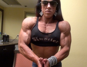 Tattooed female bodybuilder Carla is posing for you in short shorts and high-heeled shoes that show off her ripped abs, vascular biceps and ultra-muscular legs and glutes at their best.  Looks so nice, you may want to watch twice.