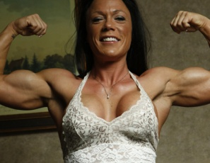 Tattooed female bodybuilder Bella poses nude and barefoot to show you how flexible she is, how powerful her pecs are, how vascular her muscular biceps and legs are, how ripped her abs are, and how good her big clit looks in close-up.