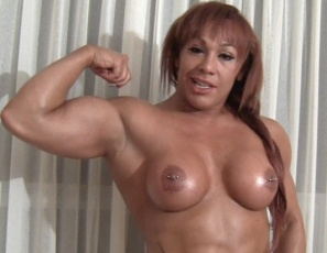 Tattooed female bodybuilder Rita likes posing nude in front of her bedroom window, showing off the powerful muscles of her pecs,  legs,  glutes, biceps and abs. She's wondering which of her admirers will burst in first. Will it be you?