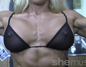 Tattooed  female bodybuilder Jill Jaxen works her muscular legs, glutes, and  vascular biceps in the gym, then poses in panties to show off her powerful pecs and ripped abs.