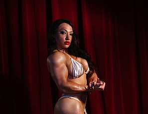 Sexy Brandimae is posing on stage flexing her powerful biceps and strong quads when she experiences a series of