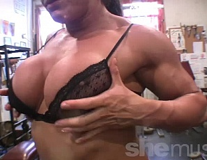 Female bodybuilder Big Tinah is building the big, vascular muscles of her biceps, pecs, ripped abs, glutes and legs in the gym. And she's posing in nothing but sheer panties to show you the results, her tattoos, and her muscle control.