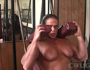 Muscular cougar Dana works hard in the gym and loves showing of the results of that hard work. Completely nude, Dana poses showing of her big biceps, powerful quads, and all around impressive physique.