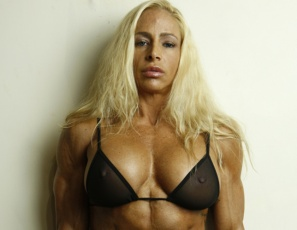 Professional female bodybuilder Jill Jaxen poses in the SheMuscle gym, showing you how ripped and vascular her pecs, legs, glutes, and abs are. Her compass tattoos are on her biceps, but you'll want to look at every big, gorgeous muscle.