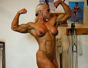 Bodybuilder Nicole Savage likes to work out in the gym in the nude which is a great way to check out her incredible muscle and vascularity. We're treated to exquisite views of ripped biceps, glutes and legs. We also catch a glimpse of Nicole's pierced and well-developed big clit.