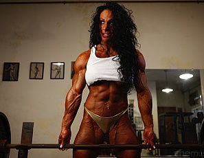 Professional bodybuilder Debbie Bramwell is looking hot and she that you're watching her get pumped. She's working the spectacular Bramwell biceps, triceps and abs - just look at those incredible peaks as she poses. Debbie is certainly something special!