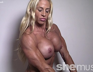Professional female bodybuilder Jill Jaxen is posing for you in the bedroom, showing off her muscular pecs, legs, glutes and abs, her big, vascular biceps, and her tattoos.