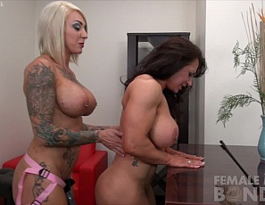 Tattooed muscular model Dani Andrews orders powerful BrandiMae over to the table, teases her wet pussy with a huge black strap-on dildo and then proceeds to fuck BrandiMae until she is screaming with delight. What more can be said than