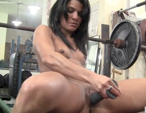 Flexible Vita's posing, showing off her biceps muscles and masturbating at the gym when she brings out a big toy, saying,