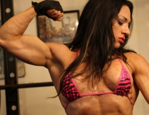 Tattooed female bodybuilder Ripped Vixen is posing in the gym. Her abs are ripped and vascular, her pecs and biceps muscles are big, but what's on her mind is penetrating her pussy with a big black dildo as she spreads her muscular legs and masturbates her pierced big clit.