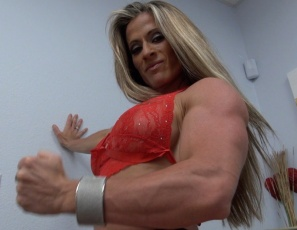 Professional female bodybuilder Maria G poses for you in panties and heels in the bedroom, showing you the rock-hard muscles of her vascular biceps, her ripped abs, her powerful pecs, legs, glutes and calves, and her tattoo. Speaking of rock-hard…