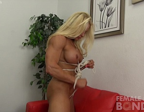 Naked professional female bodybuilder Jill Jaxen is still bound, and struggling with the ropes. As she works herself free you can see her powerful pecs, ripped abs, vascular biceps, muscular, tattooed legs and glutes struggle and strain until she is finally free.
