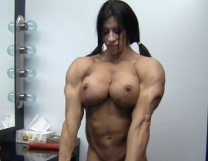 Female bodybuilder Angela Salvagno's getting ready to go out and cheer for her team, but posing and touching the big, ripped, hard muscles of her biceps, pecs, legs, glutes and abs gets her so hot she just has to take off her cheerleading outfit and masturbate her wet pussy. That's some good cheer.