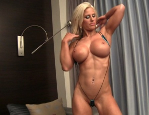 Megan Avalon's naked in the bedroom, posing, and rubbing her muscles with oil, stroking her pecs, biceps, abs, legs and glutes, and playing with her pussy and ass, squatting over your face so you can see her oil-rubbed perfection in close-up.