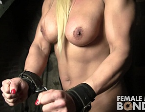 Too bad female bodybuilder Slave Lauren can't get out of the dungeon. Her muscular biceps, glutes, and pecs aren't much help when her legs are chained together in her shoes. You'll still enjoy looking at her naked muscles in close-up.