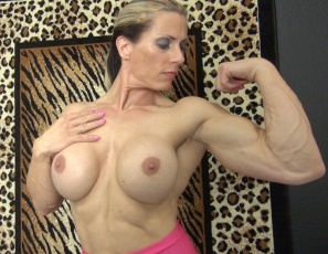 Female bodybuilder Sophie poses for you against a wild animal-print background, showing you her big, vascular biceps, her powerful pecs, her ripped, tattooed abs, and how wildly good her muscular legs, glutes, and calves look in high-heeled shoes.