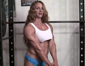 Ripped female bodybuilder IronFire works out and poses in the gym, showing off her huge vascular biceps and delts, her shredded, tattooed abs,  and  her muscle control of her powerful pecs. She's fired up – are you ready to go?