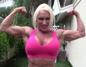 Ripped female bodybuilder Ashlee Chambers turns coach, trying to get a couple in shape. She's so strong she can lift and carry both of them, so she decides to use them as weights to strengthen the already massive, vascular muscles of her pecs, biceps, abs, legs, glutes and calves, and poses to show them – and you - the results.