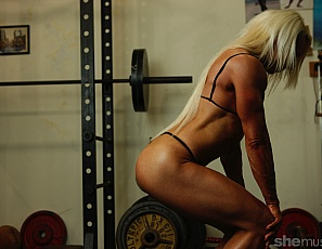 Female bodybuilder Nathalie Falk is in the gym in panties, working the ripped, mature muscles of her vascular biceps, tattooed abs, glutes, and legs, and posing for you.