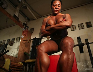 Female bodybuilder Carmella Cureton poses nude for you in the gym and in the dungeon, showing off her big ebony biceps, pecs, glutes, legs, and calves.Then she shows you her kinky side, sporting a huge black dildo in the dungeon!