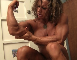 Female bodybuilder MuscleFoxx is in the bedroom for a virtual session with you, posing nude to show off her ripped, vascular legs, glutes,  calves and abs, her muscle control of her powerful pecs and her 17-inch biceps, as well as a glimpse of her pretty kitty.