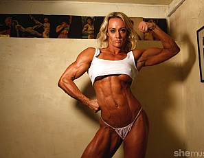 Female Bodybuilder Carmen is posing in white panties in the bedroom, showing off her vascular biceps, ripped abs, and muscular legs and glutes. The fashion forecast calls for muscles.