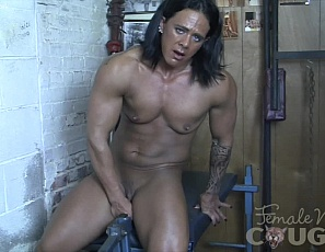 Female muscle porn star and bodybuilder Goddess of Iron is naked on the leg press in the gym, masturbating her big clit and using a toy to penetrate herself while you enjoy watching in close-up and look at her ass, the mature muscles of her pecs, glutes and legs, her ripped, tattooed abs, and her vascular biceps.