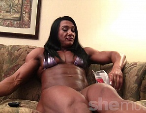 Ripped professional female bodybuilder Alina Popa is in her hotel room doing what she does to relax: watching TV and