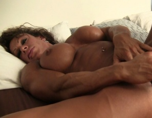 In the bedroom, female bodybuilder MuscleFoxx masturbates her big clit and   penetrates her wet pussy with a big glass toy while you watch in close-up and enjoy looking at her vascular biceps, powerful pecs, ripped abs and muscular ass and legs.