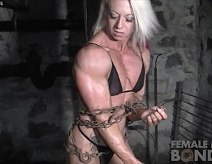 Female bodybuilder Nathalie Falk is in chains and panties in a dungeon, but she's a Professional, so she keeps trying to break free, using the vascular, tattooed muscles of her pecs, legs, biceps, and ripped abs. When she succeeds, she poses.