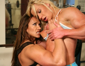 Bodybuilders Amber Steel and Delphine are going girl/girl again. This time they're working their biceps in the gym, spotting each other on the bench press, when they can't help themselves. Lots of sucking and biting – if you like the look of long pink tongues on pink and pretty big clits, you'll like these photos. After oral fun, the girls do an all-nude posedown. You be the judge.