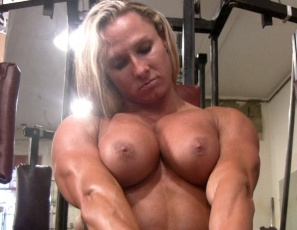 Female bodybuilder Darkside Milinda is tattooed and muscular, and she's training and posing nude in the gym, giving you a close-up look at her training regimen, at her powerful pecs,  big biceps, ripped abs, masturbation, and strong legs, and at her big clit, which she rubs until it gets hot, wet and even bigger.