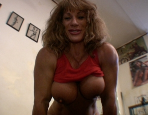 Female bodybuilder Wild Kat is in the gym, working her mature, vascular biceps muscles with heavy dumbbells and posing to show the results.