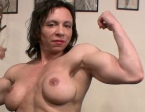 Female bodybuilder Alexis B is working out in the gym to get her hard, mature muscles even bigger, working her biceps and posing to show you how vascular and ripped they are, and how strong her pecs, abs and legs are.