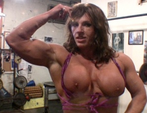 Female bodybuilder Laurie pumps up and poses in the gym, working her traps and powerful pecs and showing off her muscle control and the massive muscles  of her biceps, legs and calves, then peeling off her panties to so you can see her bare kitty.