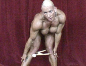 Professional Female bodybuilder Nicole Savage poses on stage to her favorite music, displaying the vascular, ripped, tattooed muscles of her biceps, pecs,  legs,  glutes,  biceps,  calves and abs, and giving you a glimpse of her sweet pussy. Think you could get closer? Don't stop believing.