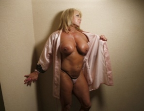 In the bedroom, bodybuilder Li'l Doll starts off wearing a pink robe, a pink ring and high-heeled shoes, and posing for you. She takes off the robe and she's naked and vascular – her pecs, legs, glutes, calves and biceps are looking good. So's her big clit, and when she plays with it and masturbates her pussy, she's really in the pink.