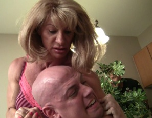 Female bodybuilder, muscle porn star and fem domme Wild Kat is angry with what her dumb helpers are doing to her tree, so she humiliates them, scissors them, chokes them with her powerful biceps and pecs, and makes them worship the muscles of her vascular abs, legs and calves. What should they do – take it or leave it?