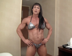 Professional female bodybuilder Tazzie Colomb is posing for you in her bedroom after the Arnold Classic, drinking coffee, and showing you how vascular and ripped her pecs, legs, biceps and abs muscles are.  Tazzie loves talking to you – and you love coffee with Taz, don't you?