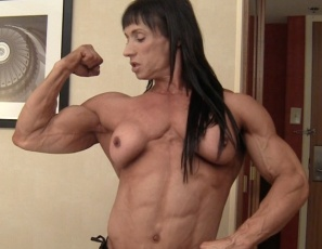 Enjoy a relaxed moment with professional female bodybuilder Tazzie Colomb in the bedroom as she talks about how much her fans mean to her and how she likes her coffee (strong, no surprise) Then she poses half-nude, showing you her massive muscles - her vascular biceps, powerful pecs, big legs and ripped abs.