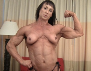 Professional female bodybuilder Tazzie Colomb, just back from the Arnold Classic, poses for you in the bedroom so you can appreciate the muscles of her powerful naked pecs, vascular biceps, ripped abs and tight glutes.