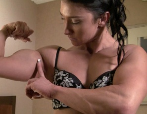 "Bodybuilder Jenna is posing barefoot in the bedroom, taking off her sexy panties until she's nude, flexing her big biceps and showing off her tight abs and strong legs and glutes. The camera hovers between her naked legs as she asks, ""Is this where you'd like your head?"""