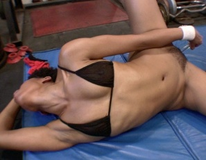 Melanie's on the gym floor, penetrating herself with a big glass dildo and moaning loudly as she masturbates. She's so flexible that she finds lots of ways to insert her toy, then sucks her own juices off it. Watch her strong ebony legs, glutes and biceps as she rides it hard and poses, flexing her biceps, and enjoy her wet pussy in close-up.